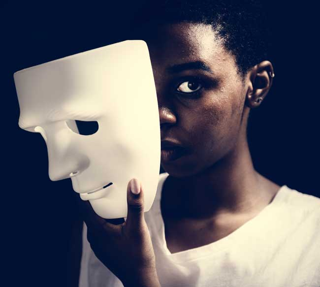 """image of young black woman with white mask pulled away from face for blog article entitled """"Imposter Syndrome"""" Jessica Banks is a Reiki Master, Yogini, and Psychic Energy Healer"""
